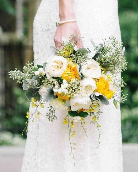 bride holding yellow flower wedding bouquet